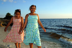 African american sisters. Two african american sisters walking along shoreline stock photography