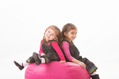 Sisters on beanbag. Portrait of sisters sitting on pink bean bag Stock Images