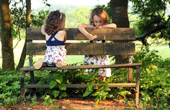 Sisters on Bench. Sisters playing together on a park bench Royalty Free Stock Photography