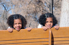 Sisters on bench swing Stock Photography