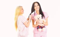Sisters, best friends in pajamas making braid, hairdo each other. Girls in pink pajamas, isolated white background. Ladies on smiling faces with plush toy bear royalty free stock images