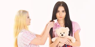 Sisters, best friends in pajamas making braid, hairdo each other. Ladies on smiling faces with plush toy bear look cute. Girls in pink pajamas, isolated white royalty free stock images