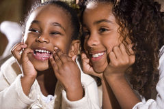Sisters with big grins. Two happy African American sisters sitting together in bedroom smiling royalty free stock photo