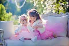 Sisters in blossom park. Cute little sisters  in apple blossom garden Stock Images