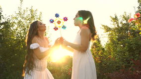 Sisters blow a toy pinwheel. Two young attractive girls blow a toy pinwheel. Girls of the sister. They are dressed in white dresses. Family time stock video footage