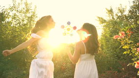 Sisters blow a toy pinwheel. Two young attractive girls blow a toy pinwheel. Girls of the sister. They are dressed in white dresses. Family time. Sunset sun in stock video