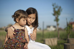 Sisters blowing dandelion. Two sisters sitting in a meadow or garden, blowing a dandelion together Royalty Free Stock Images