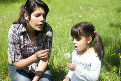 Sisters blowing dandelions. On a meadow Royalty Free Stock Photography