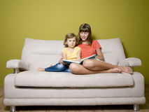 Sisters with book on sofa Stock Photo