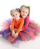 Sisters in bright tutu skirts. Two adorable sisters dressed in bright colorful tutus sitting down hugging each other, isolated on white Stock Photos