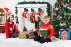 Sisters and brother beside Christmas tree Royalty Free Stock Image