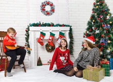 Sisters and brother beside Christmas tree Stock Photography