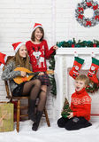 Sisters and brother beside Christmas tree Stock Photos
