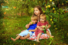 Sisters and brother in the garden. Pretty teen girl with little sister and brother resting in the garden near the apple tree Stock Image