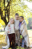 Sisters and brother hugging in plaid Stock Photos