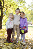 Sisters and brother hugging in plaid under autumn trees Royalty Free Stock Photography