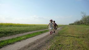 Sisters And brother running laughing, Field road at sunset, Slow motion, Two cute child in park, outdoors, kids are stock video