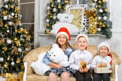 Sisters and brothers with x-mas gift boxes Stock Photos