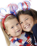 Sisters Celebrate. Closeup image of two sisters a decked out to celebrate America's Independence Day.  On a white background Royalty Free Stock Photos