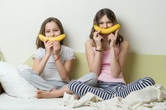 Sisters of children in pajamas play in the morning in bed. Use bananas for the smiley snark.  Stock Images