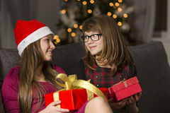 Sisters with Christmas presents looking at each other on sofa Royalty Free Stock Photos