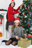 Sisters beside Christmas tree Stock Photo