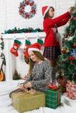 Sisters beside Christmas tree Stock Image