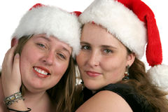Sisters At Christmastime 1. Two pretty sisters in Santa hats Royalty Free Stock Photo