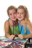 Sisters coloring together vertical. Isolated on a white background Royalty Free Stock Photos