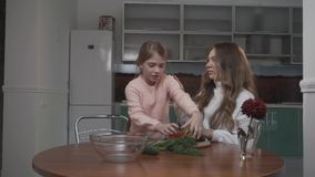 Sisters cooking vegetable salad at the table in the kitchen. The younger sister brings tomatoes to the older sister stock video footage