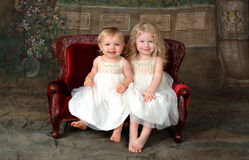 Sisters on Couch. Sisters sitting together on red velvet antique children's couch Stock Image