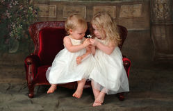 Sisters on Couch Holding Flower royalty free stock images