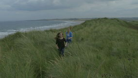 Sisters day out. Two happy sisters laugh and smile as they run along grassy dunes by the beach. The older sister is behind chasing the young girl as they run stock footage