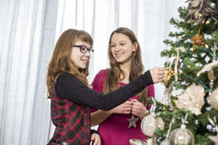Sisters decorating on Christmas tree at home Stock Photo