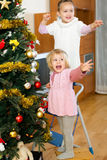 Sisters decorating christmas tree Royalty Free Stock Photos
