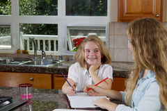 Sisters doing their homework while in the kitchen Stock Images