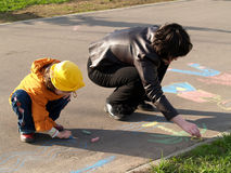 Sisters draw on asphalt. Two sisters draw on asphalt Royalty Free Stock Photography