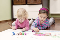 Sisters drawing  on the floor Royalty Free Stock Image
