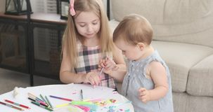 Sisters drawing together with color pencil at home. Girl holding hands of her baby sister and teaching her to draw with pencil stock footage