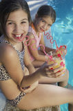 Sisters Drinking Juice By Poolside Stock Photography
