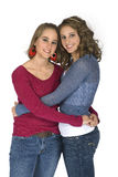 Sisters In Each Other's Arms. Two sisters embracing in each other's arms isolated on white with clipping path Stock Images