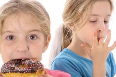 Sisters eating a doughnut Royalty Free Stock Photos