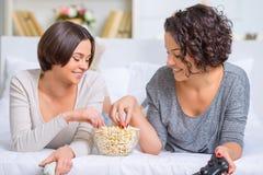 Sisters eating popcorn between videogames Stock Photos