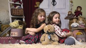 Girls are sitting among plush toys and Christmas presents, slow motion stock footage