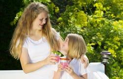 Sisters enjoying drinking lemonade outside on patio Royalty Free Stock Photography