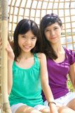 Sisters enjoying the rattan swing Stock Images