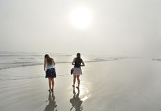 Sisters enjoying time together on beautiful foggy beach. Royalty Free Stock Photography