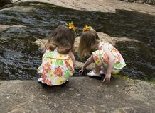 Sisters exploring. Twin sisters exploring in the water Stock Image