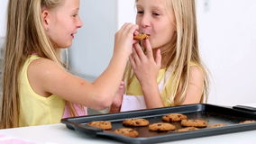 Sisters feeding each other fresh cookies