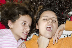 Sisters fighting in bed Royalty Free Stock Photography
